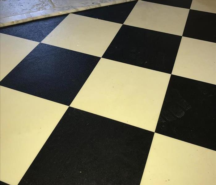 Black and white checkered floor with dirty and white marks on black portion of tiles.