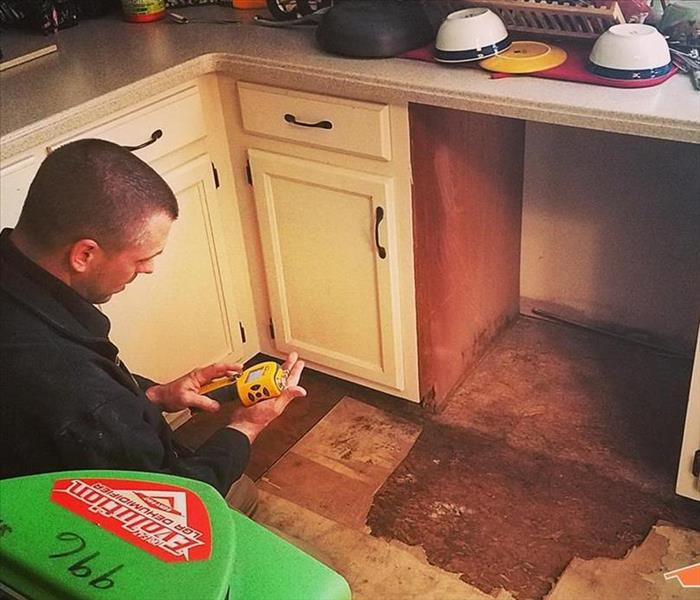 worker under sink cleaning water damage