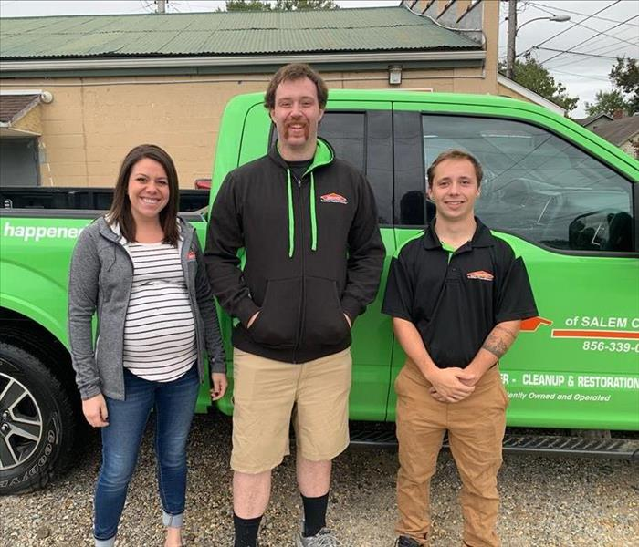 three team members in front of bright green truck
